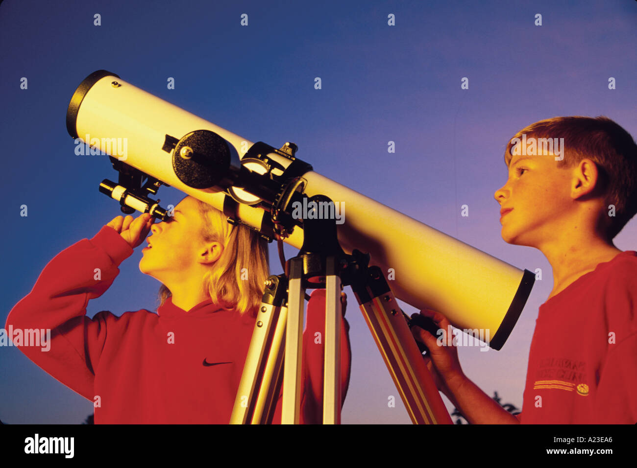 ten year old brother and eleven year old sister look at stars through telescope Santa Barbara California - Stock Image