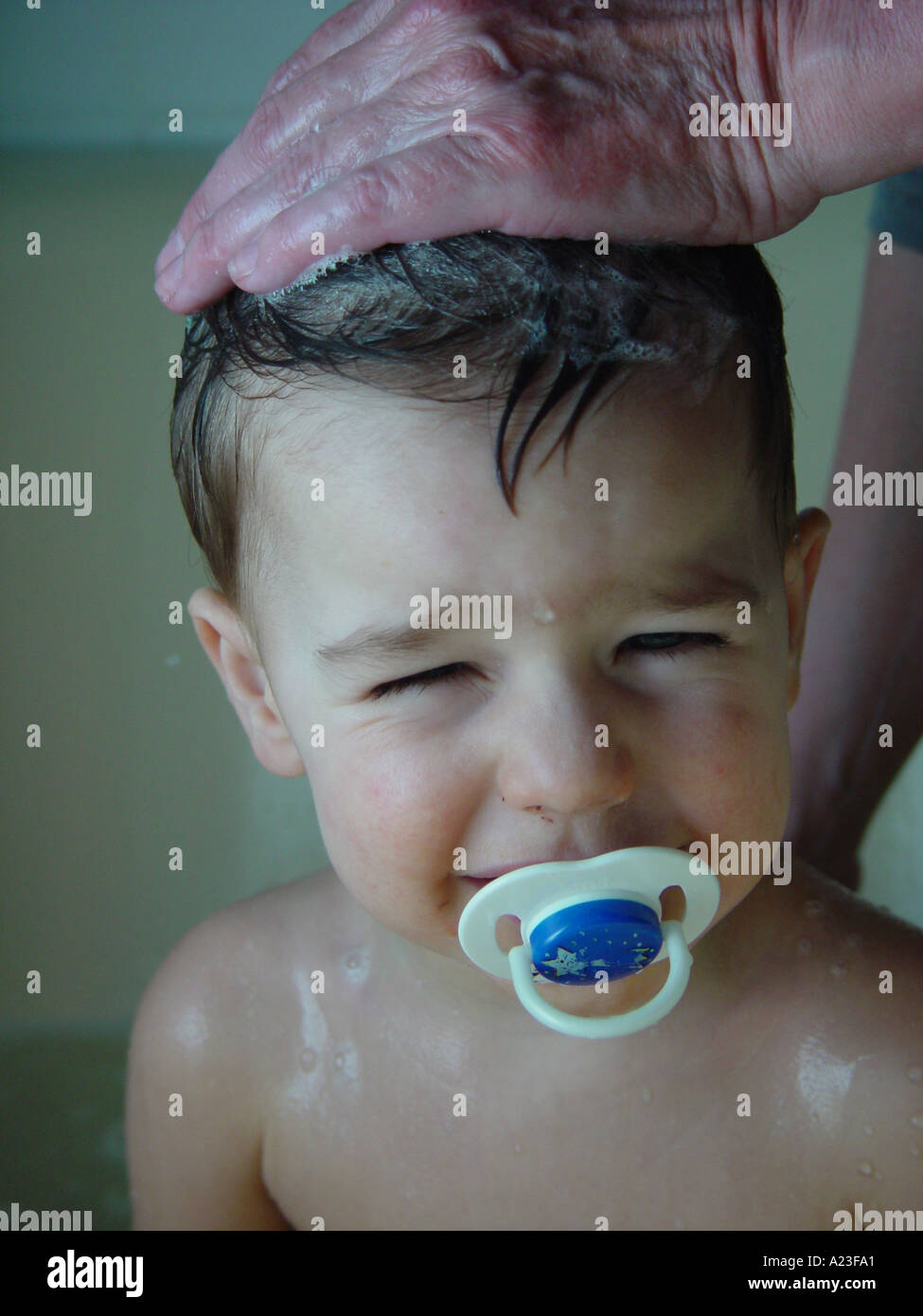 Hair wash of boy by mother in bath tube in private bathroom at home - child with pacifier (don't like washing hair) Stock Photo