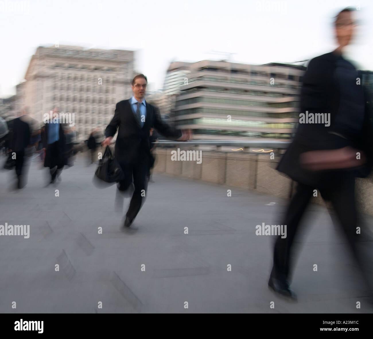 man running rushing to work across London Bridge in UK - Stock Image