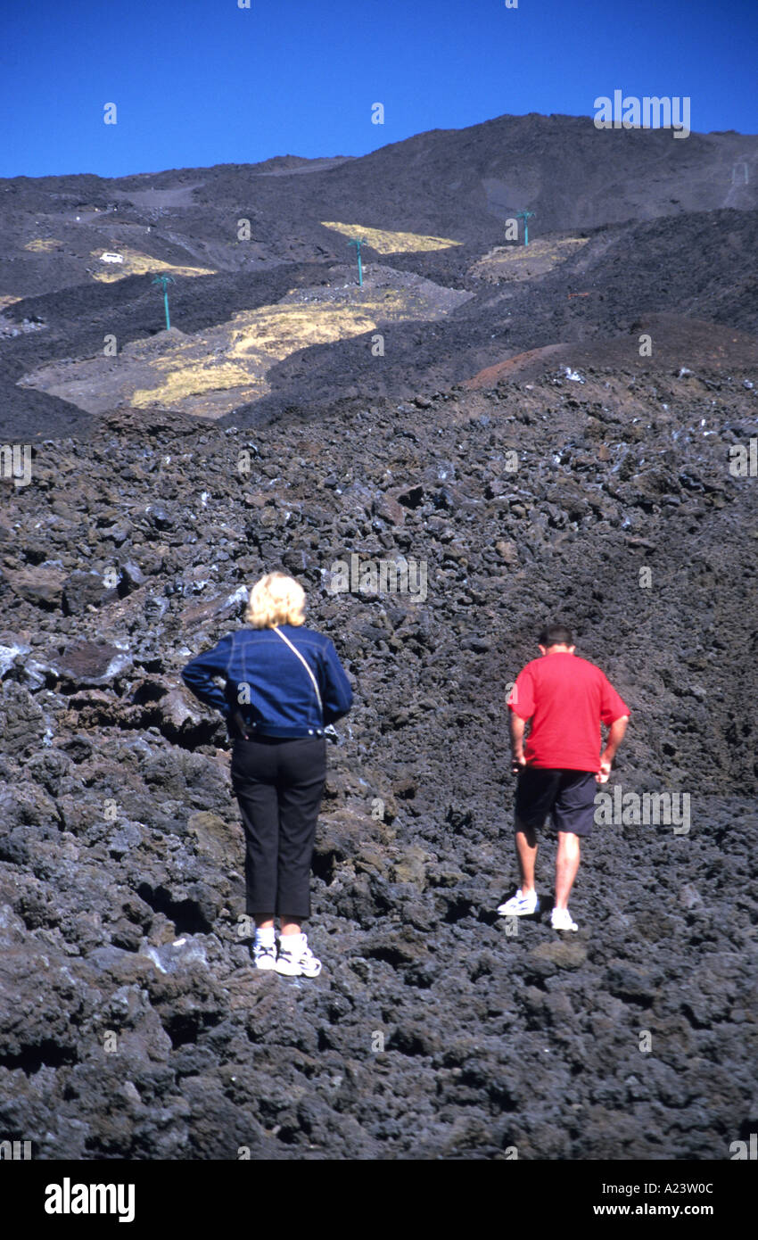 Tourists exploring the lava fields of Mount Etna after a volcanic eruption. - Stock Image