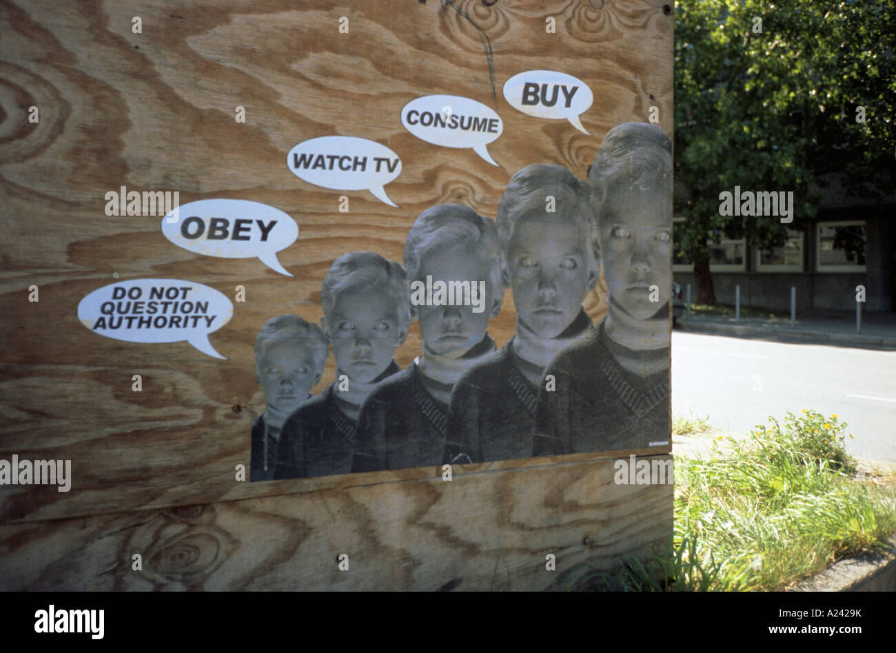 A poster on a wooden wall criticizing consumerism in Stuttgart Germany - Stock Image