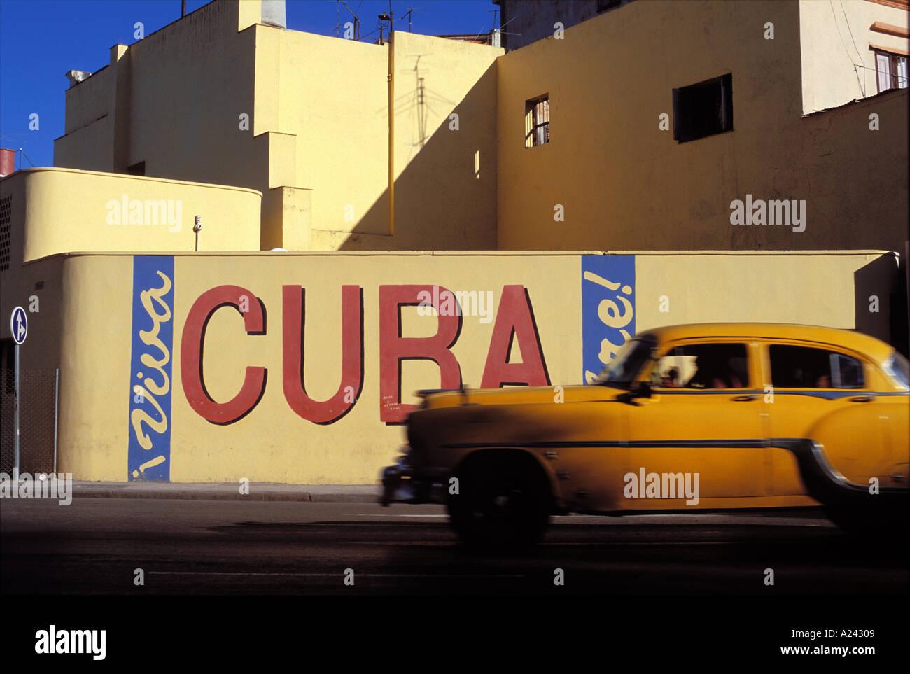 Cuba Havana 1950 s Chevrolet driving past Viva Cuba mural - Stock Image