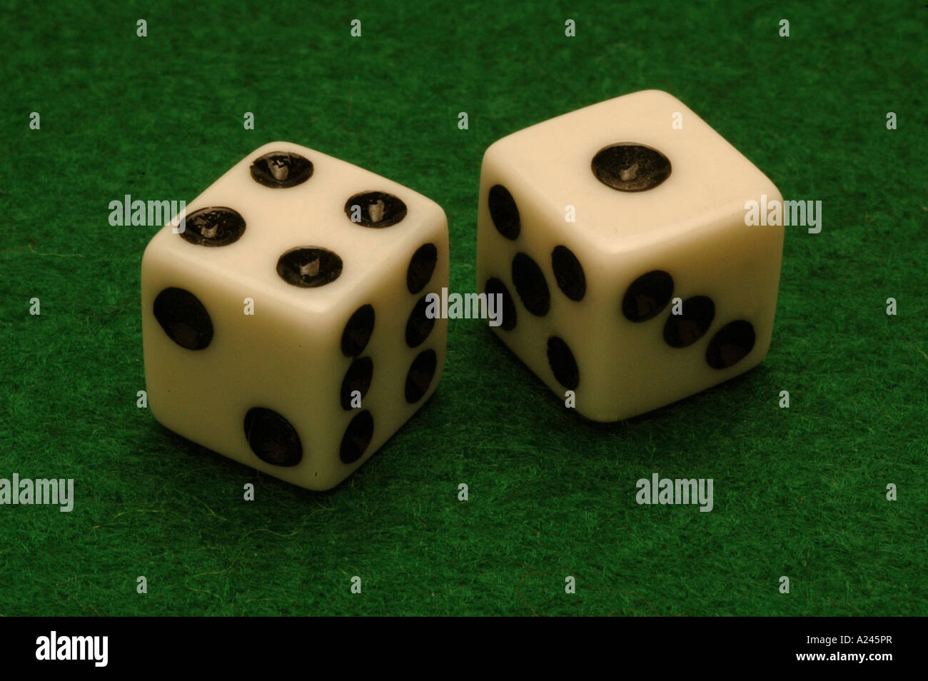 Dice on a green felt gambling table - Stock Image