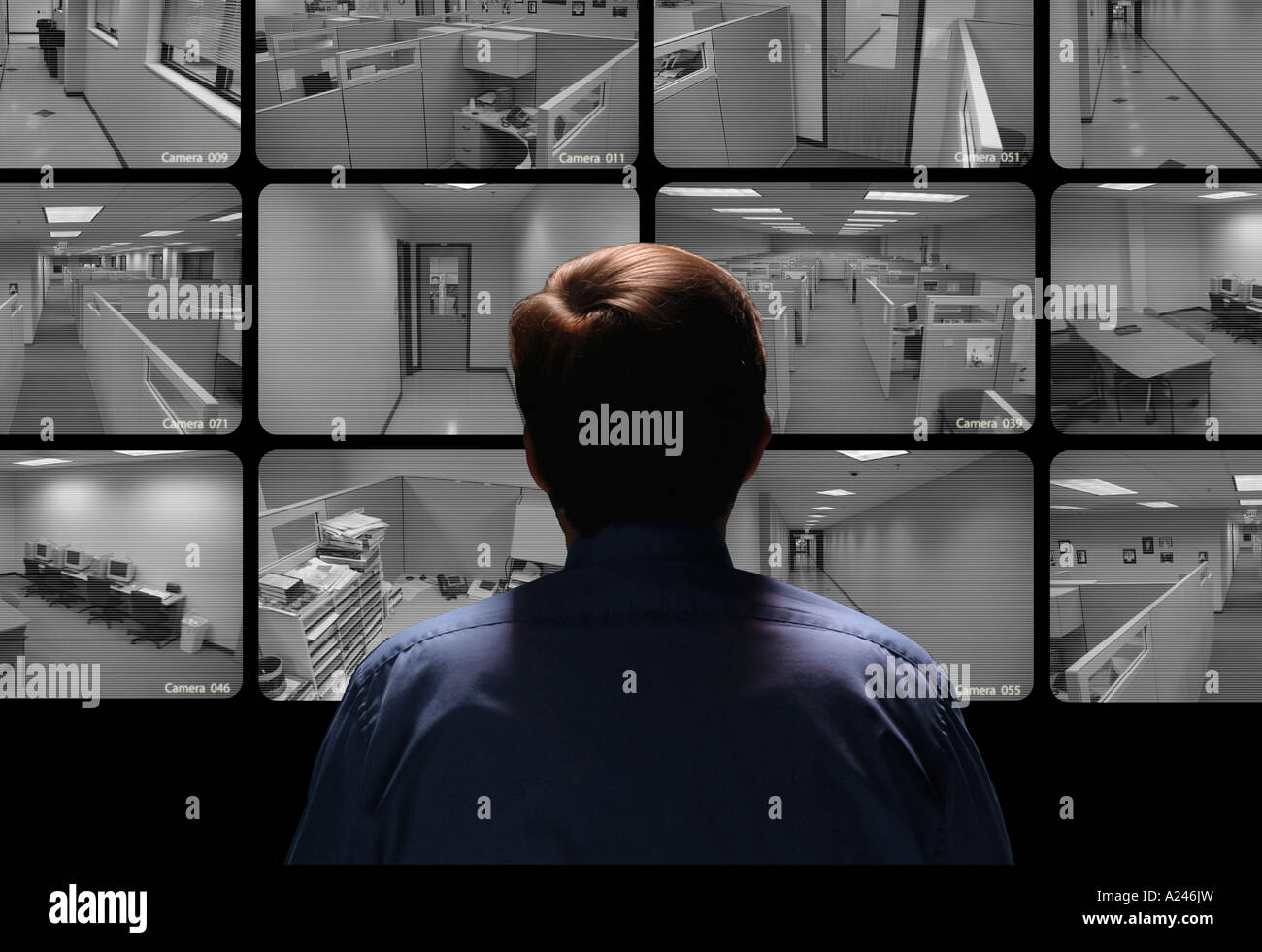 Security guard conducting surveillance by watching several security monitors - Stock Image