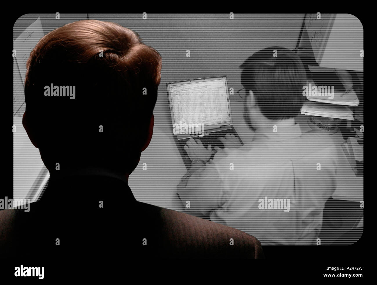 Man observing an employee work via a closed circuit video monitor - Stock Image
