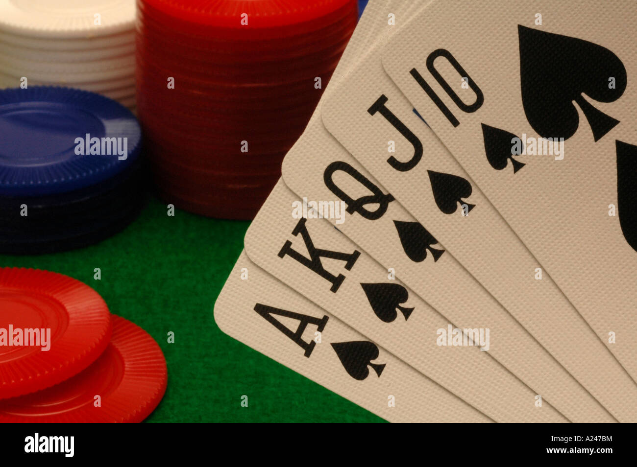 Cards and poker chips on a green felt gambling table - Stock Image