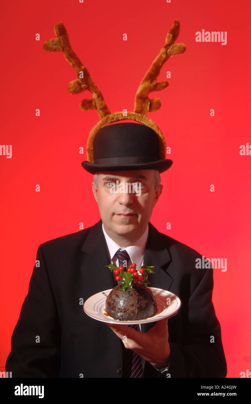 Butler wearing antlers presenting a Christmas pudding. red background - Stock Image