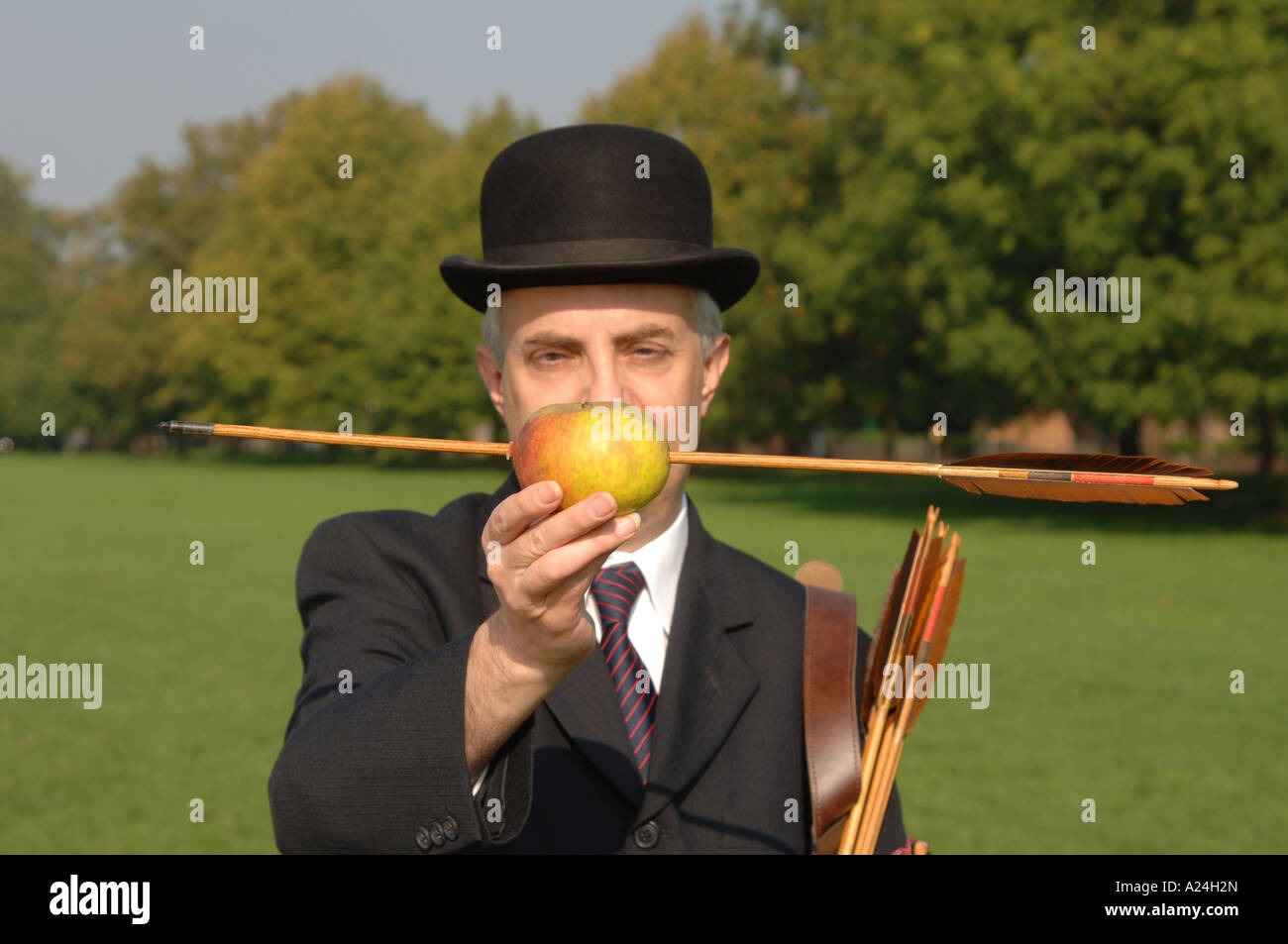 City gent holding an apple with an arrow through it - Stock Image