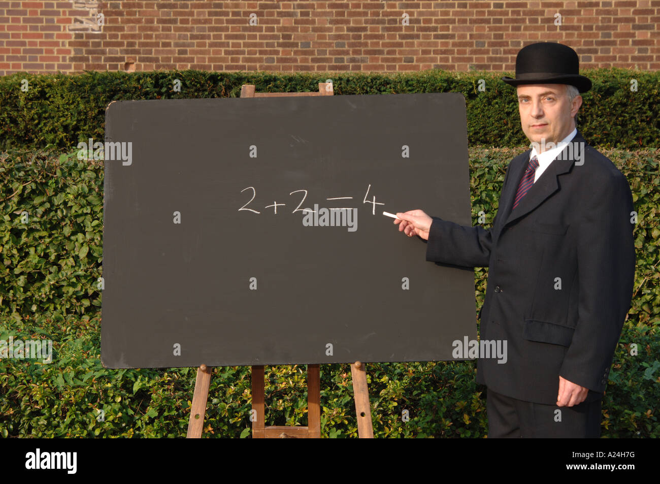City gent in suit and bowler hat explaining simple maths with traditional chalk and blackboard. 2+2 = 4. Two plus - Stock Image