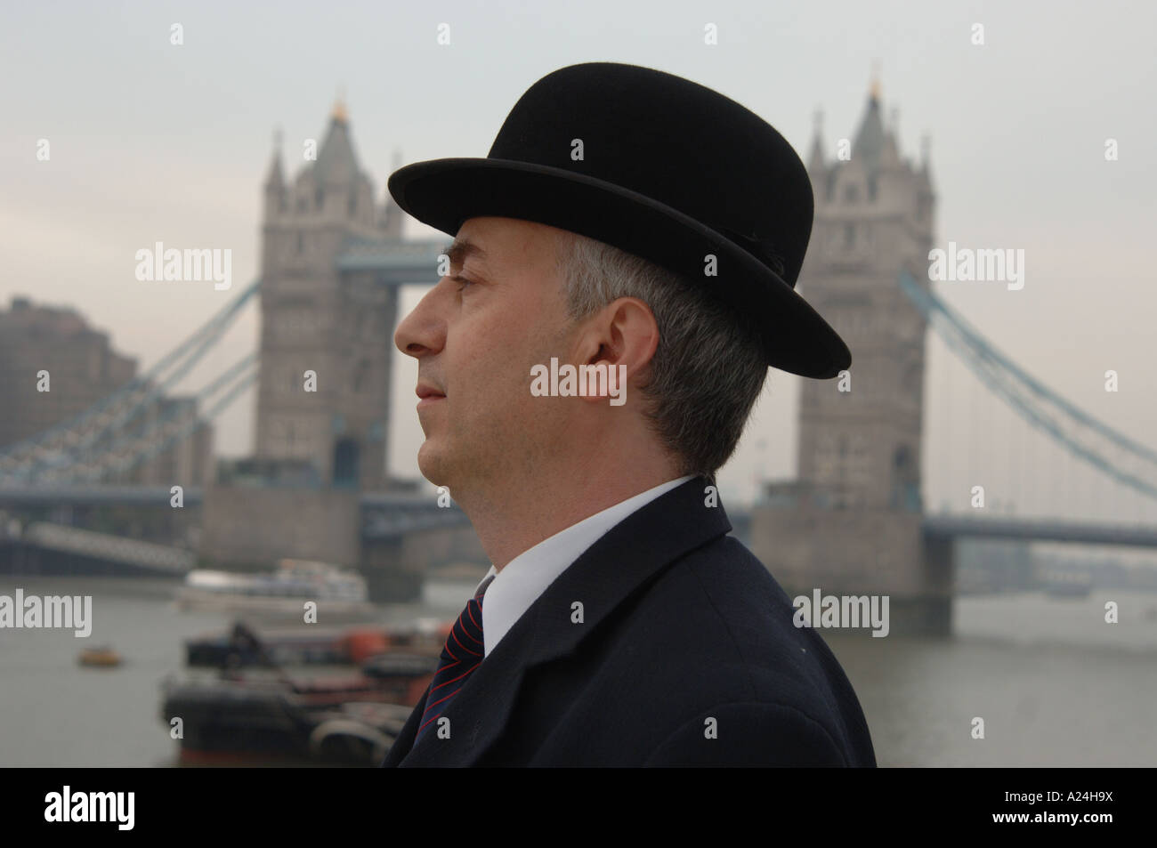 Traditional British city gent in bowler hat and business suit by Tower Bridge, London, UK - Stock Image