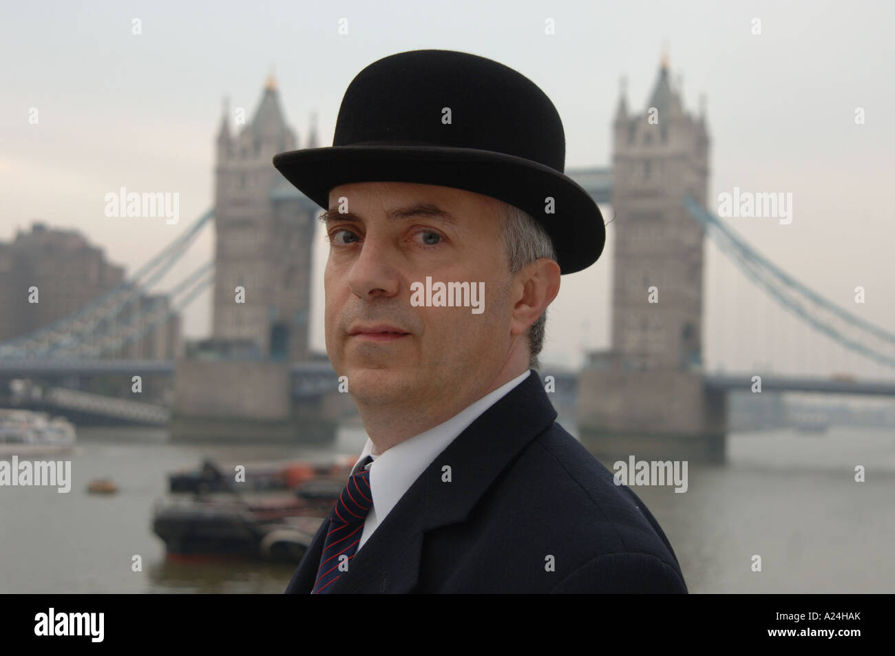 Traditional English city gent in suit and bowler hat by Tower Bridge, City of London, UK. - Stock Image