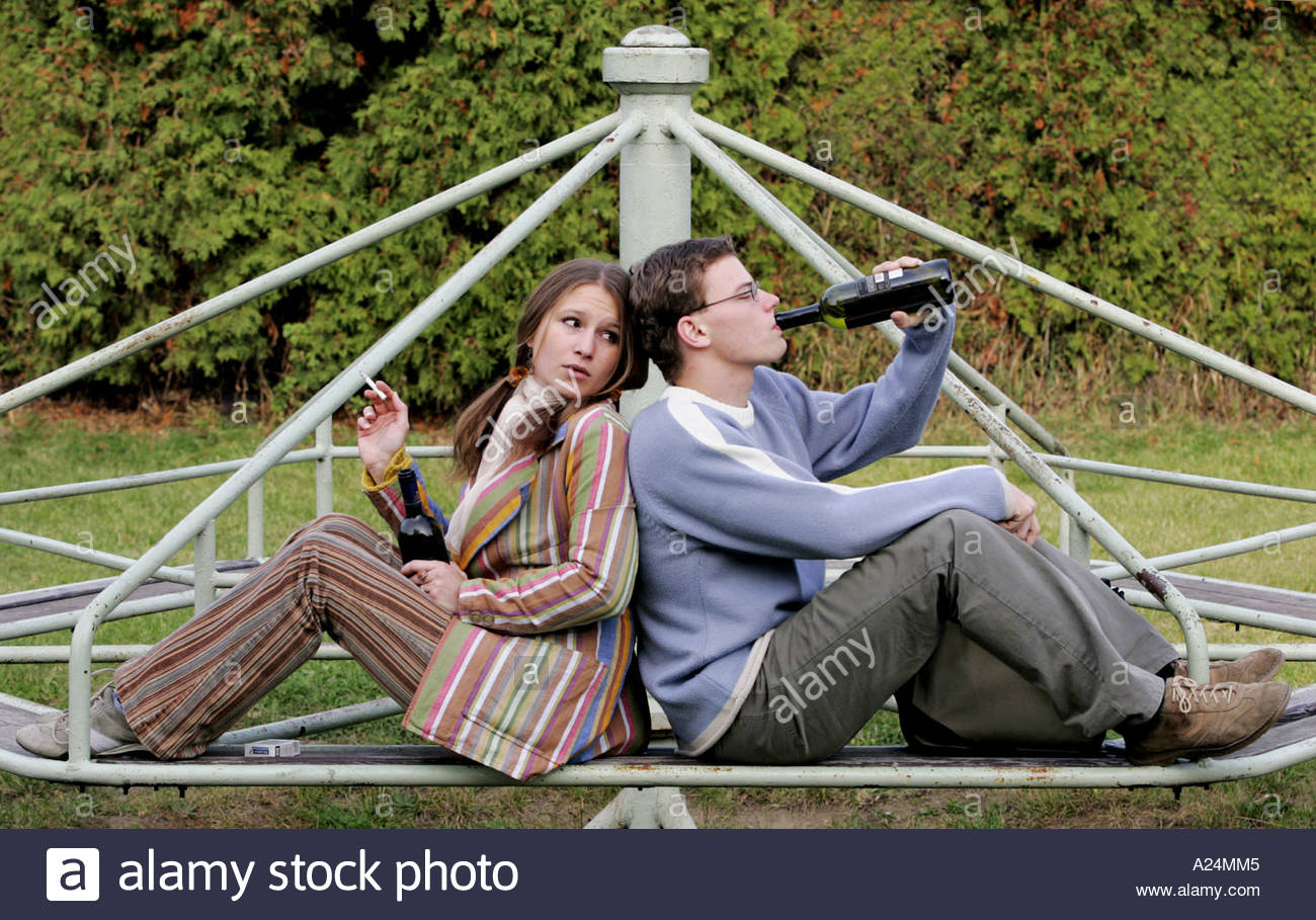 Girl and Boy Drinking in Park Stock Photo