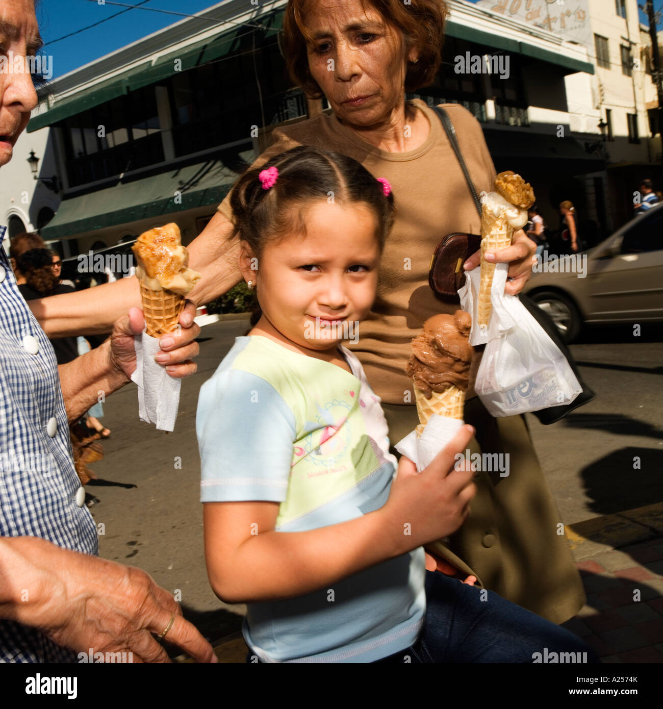 Girl eating ice-cream with her mother on the streets of downtown Mazatlan Mexico - Stock Image