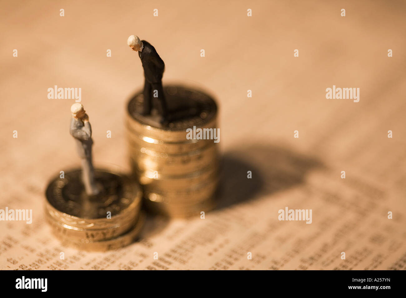 Miniature businessmen standing on coins on financial newspaper - Stock Image