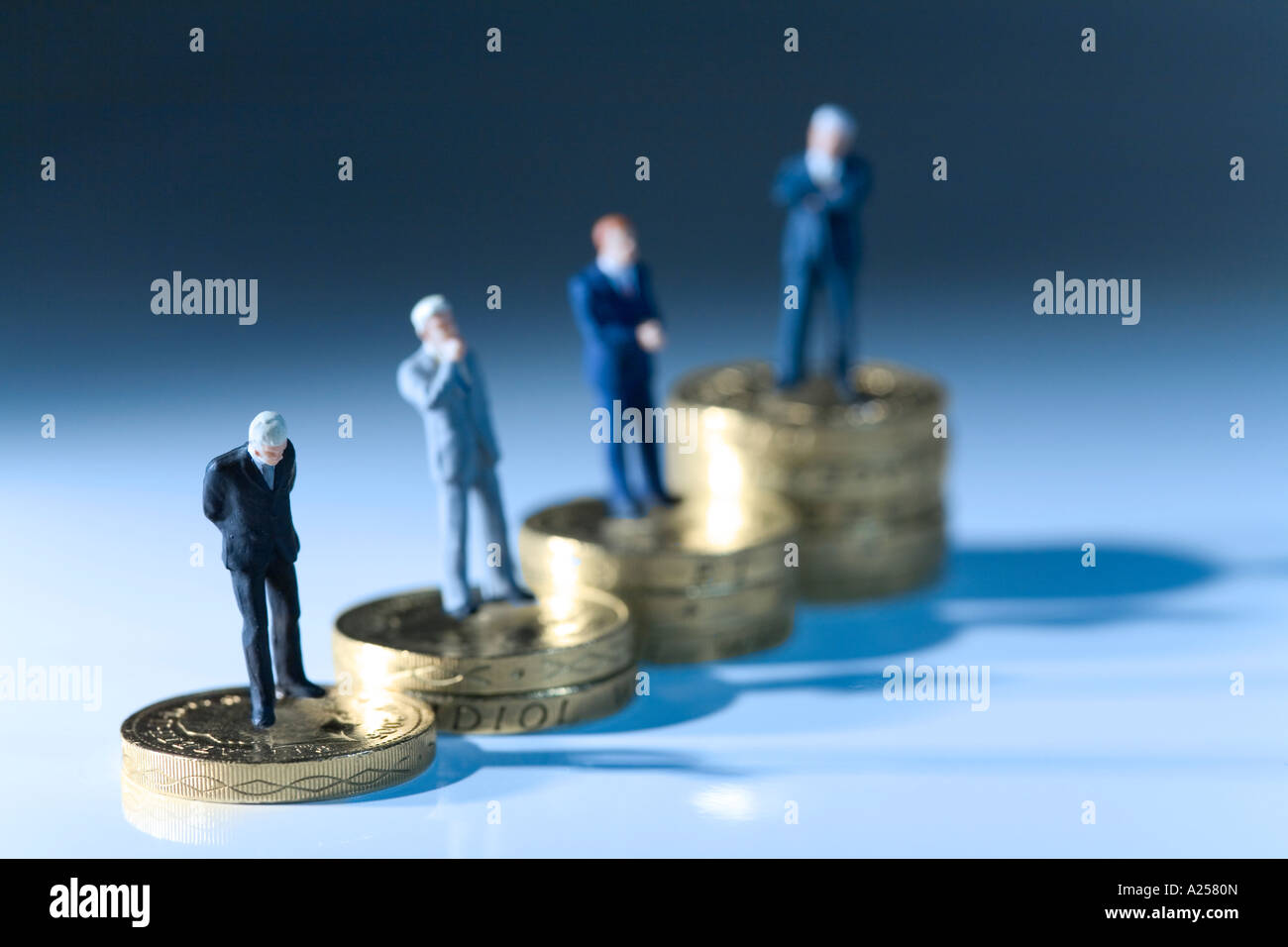 Miniature businessmen standing on coins. This photo illustrates the vast gap in wages within companies Stock Photo