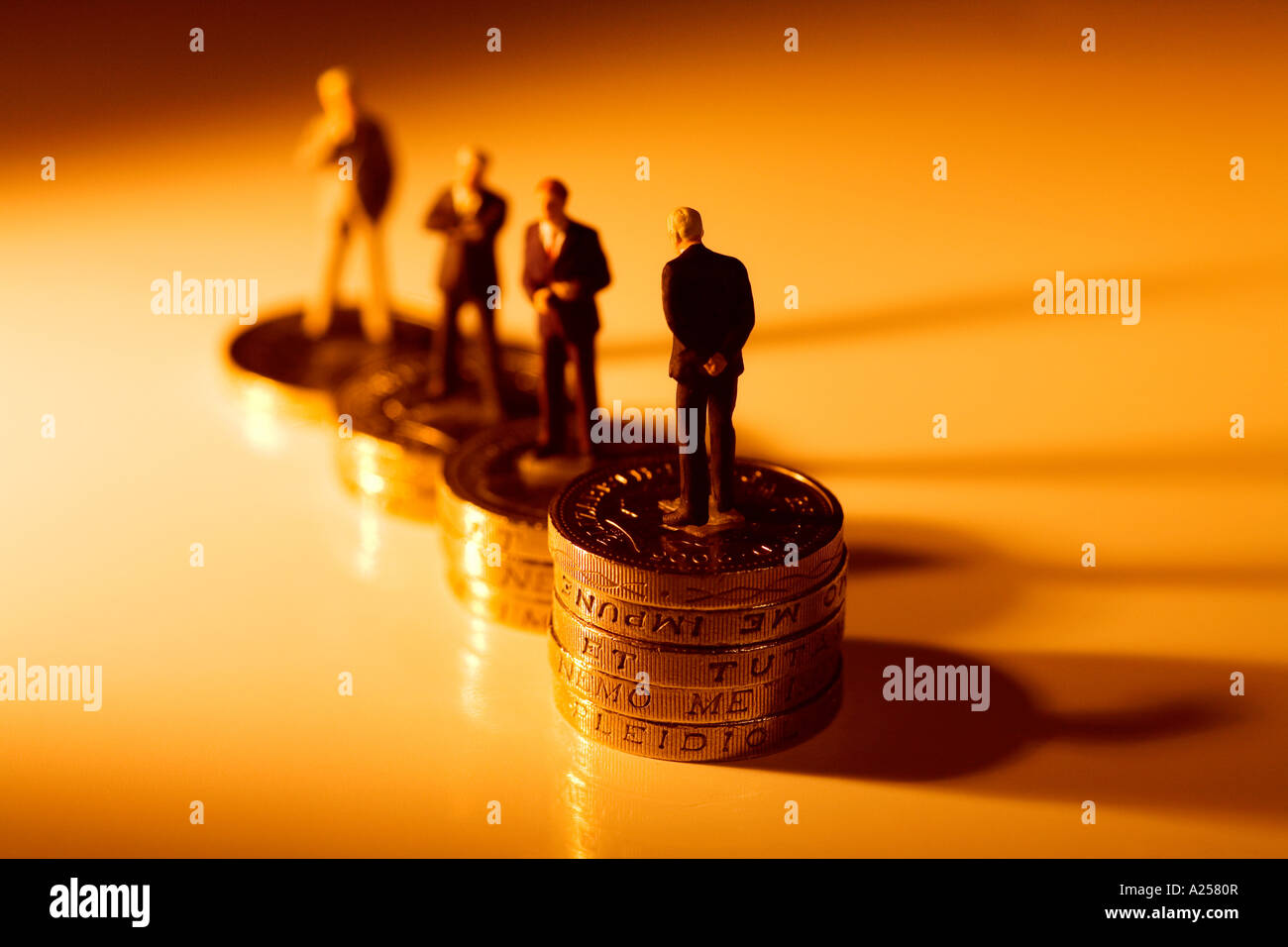 Miniature businessmen standing on coins. This photo illustrates the vast gap in wages within companies - Stock Image