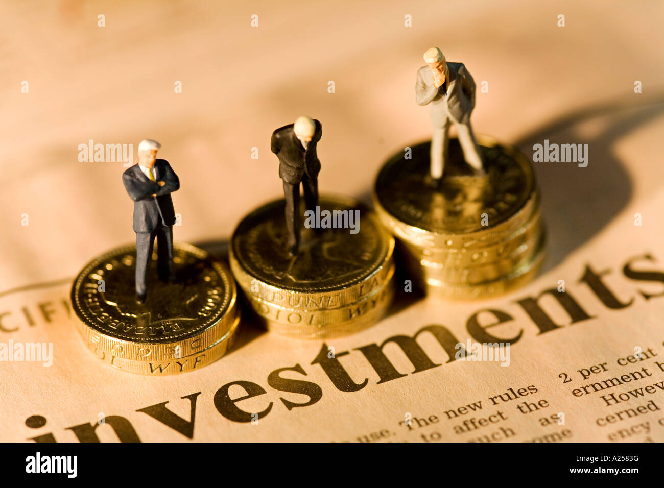 Miniature businessmen standing on stacks of coins on financial newspaper with investments headline - Stock Image