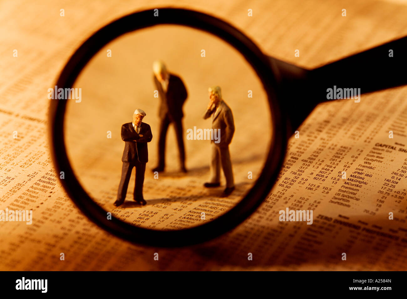 Miniature businessmen seen through magnifying glass standing on financial newspaper - Stock Image