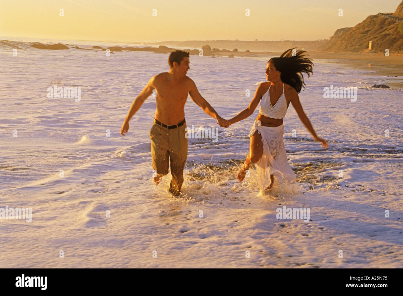 Couple enjoying happy romantic moments in waves breaking on sandy shore along Southern California coast at sunset - Stock Image