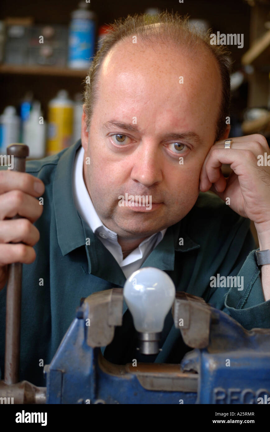 AN ELECTRICAL SHOP OWNER IN HIS WORKSHOP WITH A LIGHT BULB IN A VICE UK Stock Photo