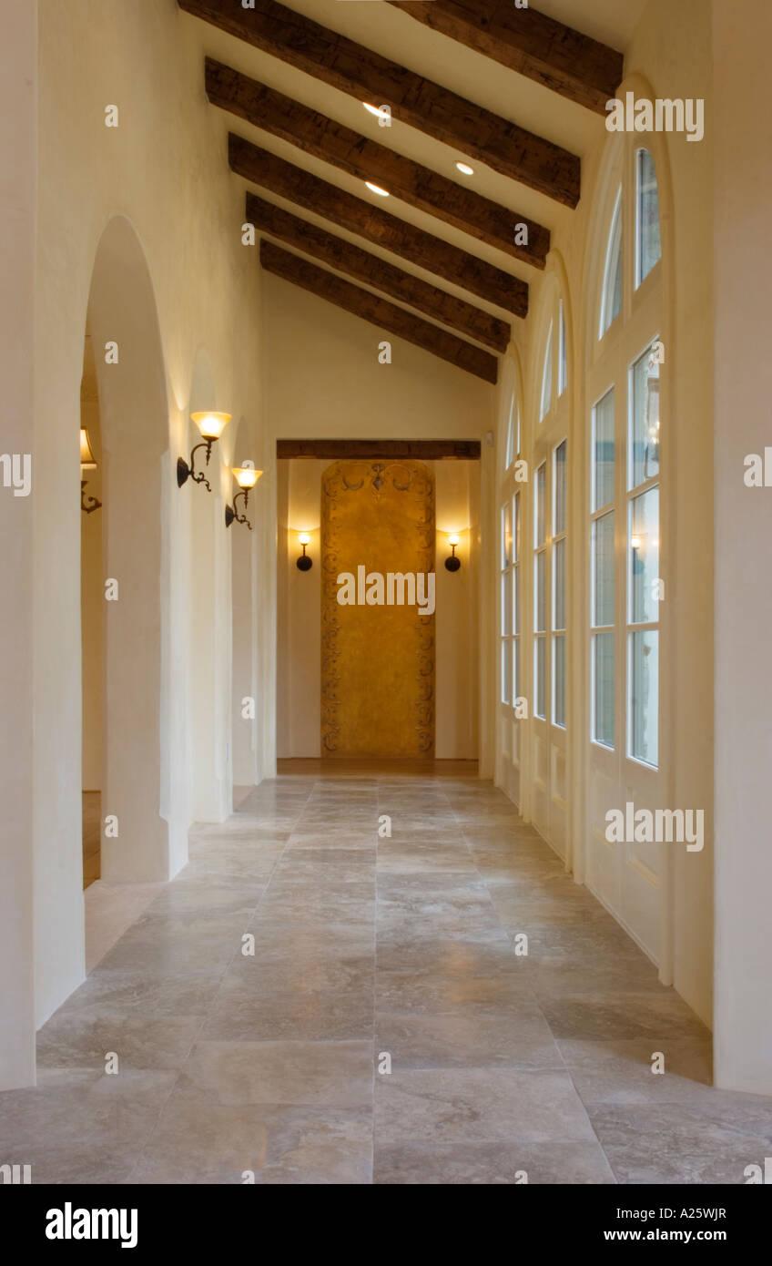 Stone floor and hallway with interior lighting fixtures and multi paned windows california luxury home
