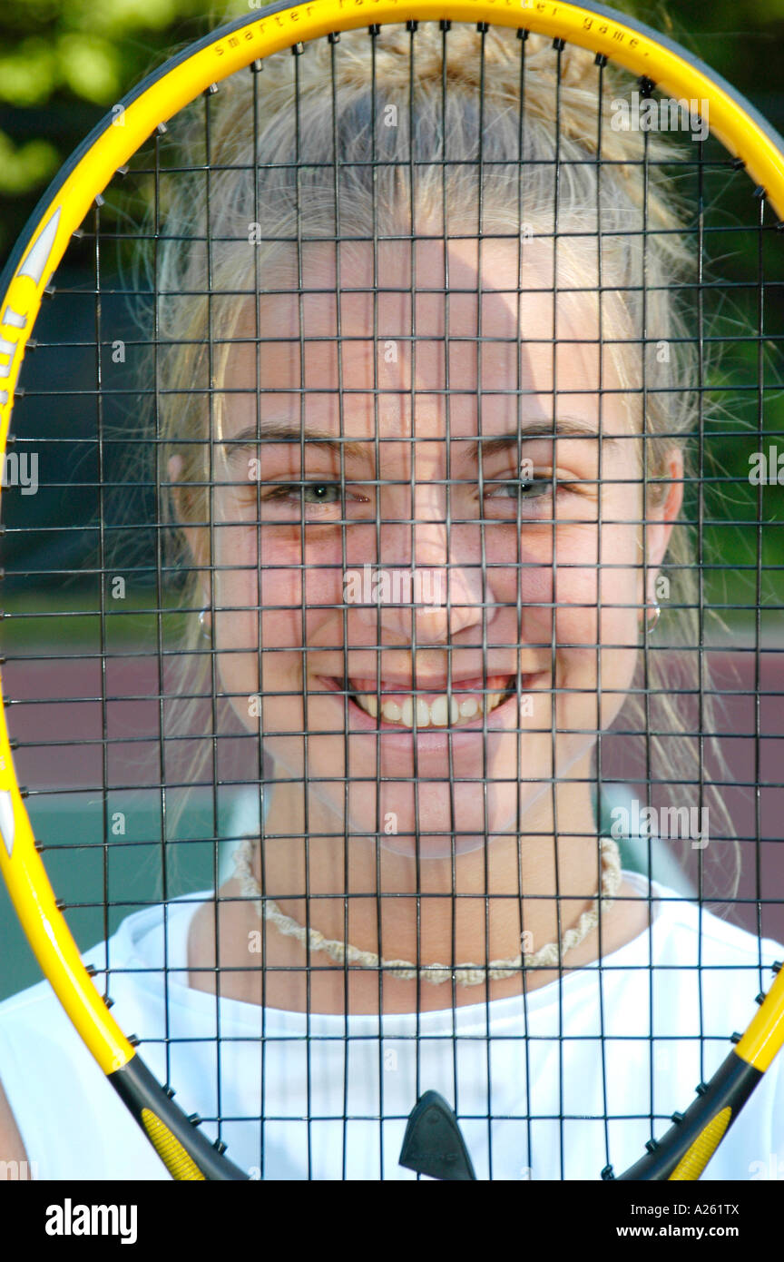 High school tennis player with tennis racket in front of her smiling face - Stock Image