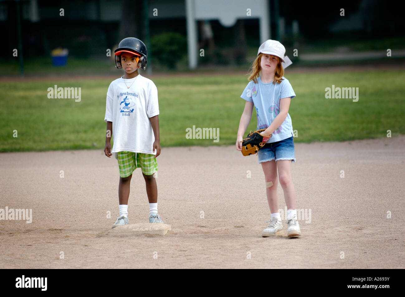 5 to 7 year old boys and girls taken baseball lessons by being introduced to T Ball little league - Stock Image
