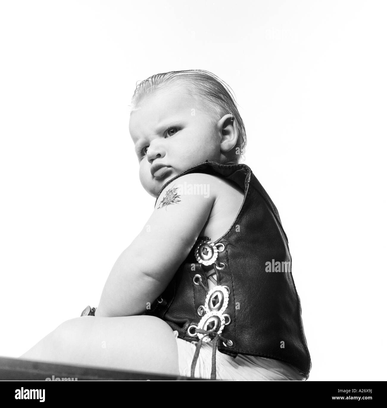 Baby boy (6 months) wearing leather vest. Stock Photo