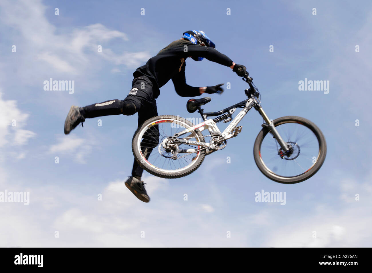 Biker performs tricky jump in the air - Stock Image