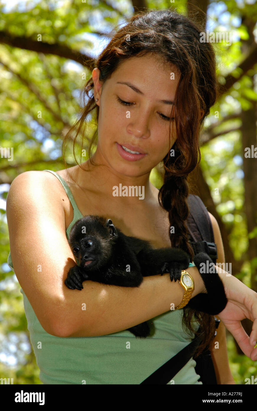 Costa Rican girl carrying a Howler monkey baby, Guanacaste Province ...
