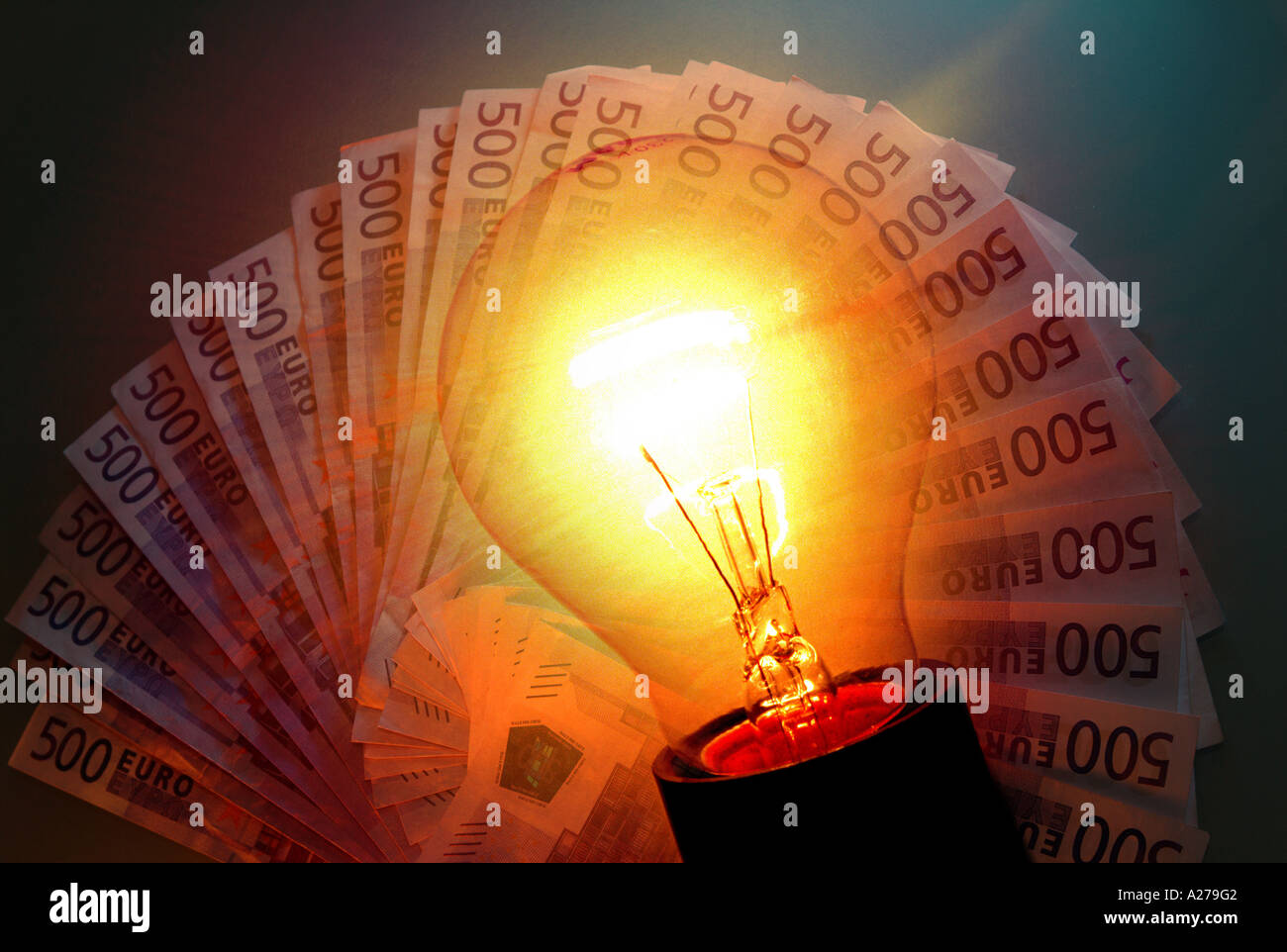 costs of energy price of electricity burning electric light bulb with big bank notes 500 euro notes in background - Stock Image