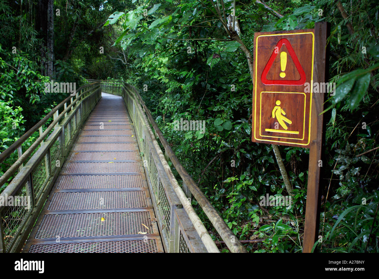 Footbridge and wooden sign for 'take care, slippery' - Stock Image