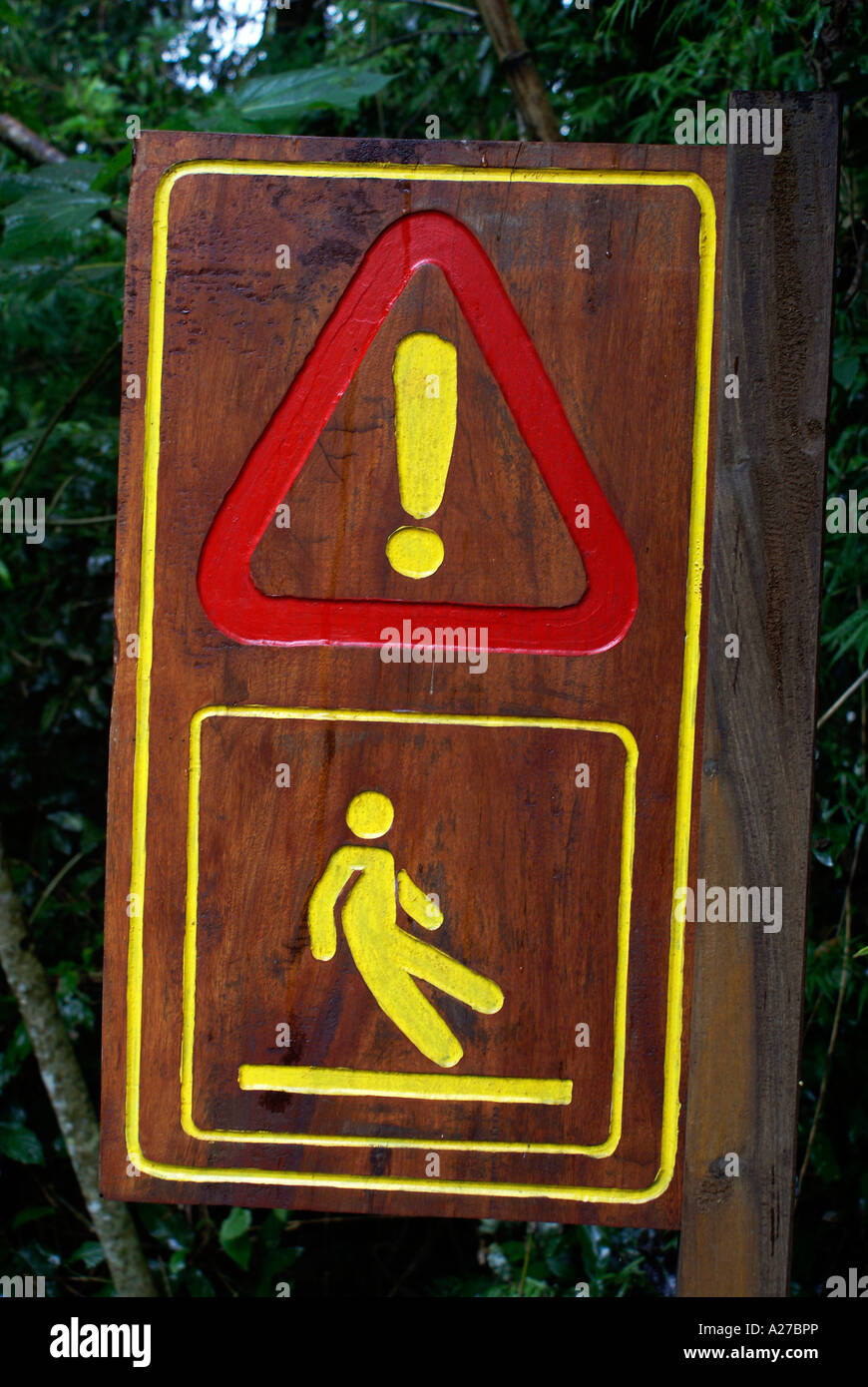 Wooden sign for 'take care, slippery' - Stock Image