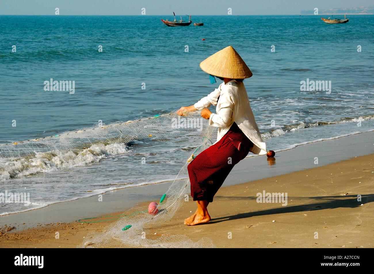 Fisher woman hauling in the fishing net, Mui Ne, Viet Nam - Stock Image
