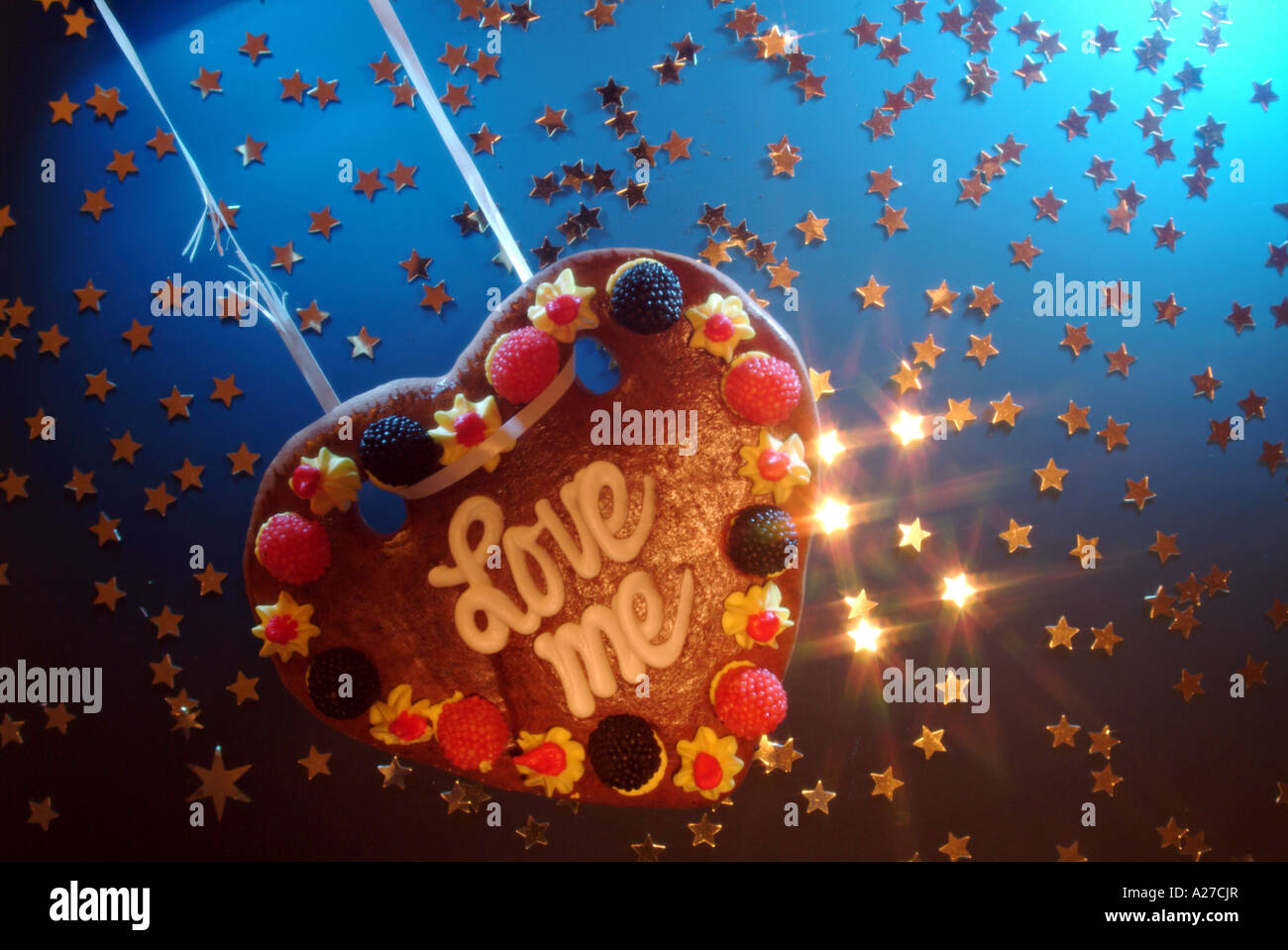 Love heart made of honey cake swinging on a broken string in stars - Stock Image