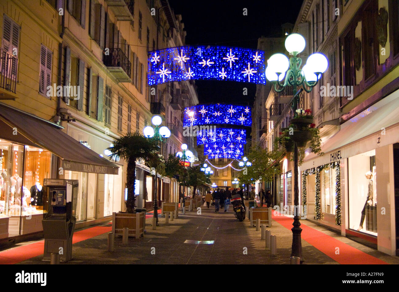 Strollers enjoying the Christmas streetlight decorations on the fashionable rue de Paradis in Nice on the French - Stock Image