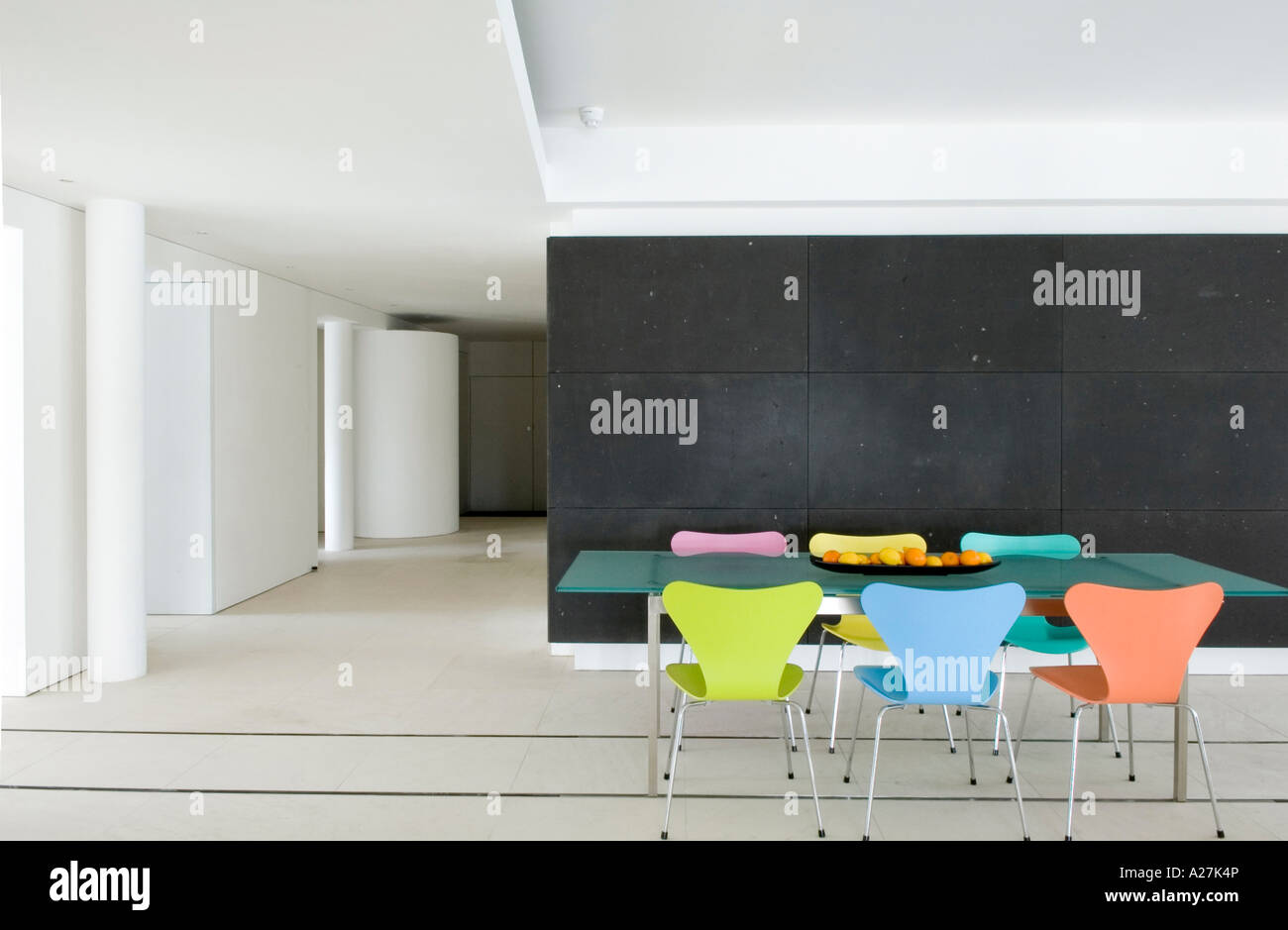 Glass dining table with coloured butterfly chairs in modern minimalist warehouse conversion - Stock Image