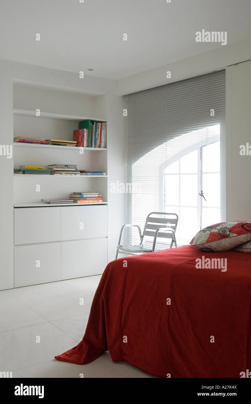 Corner of bed with red cover and shelving in minimalist warehouse conversion - Stock Image