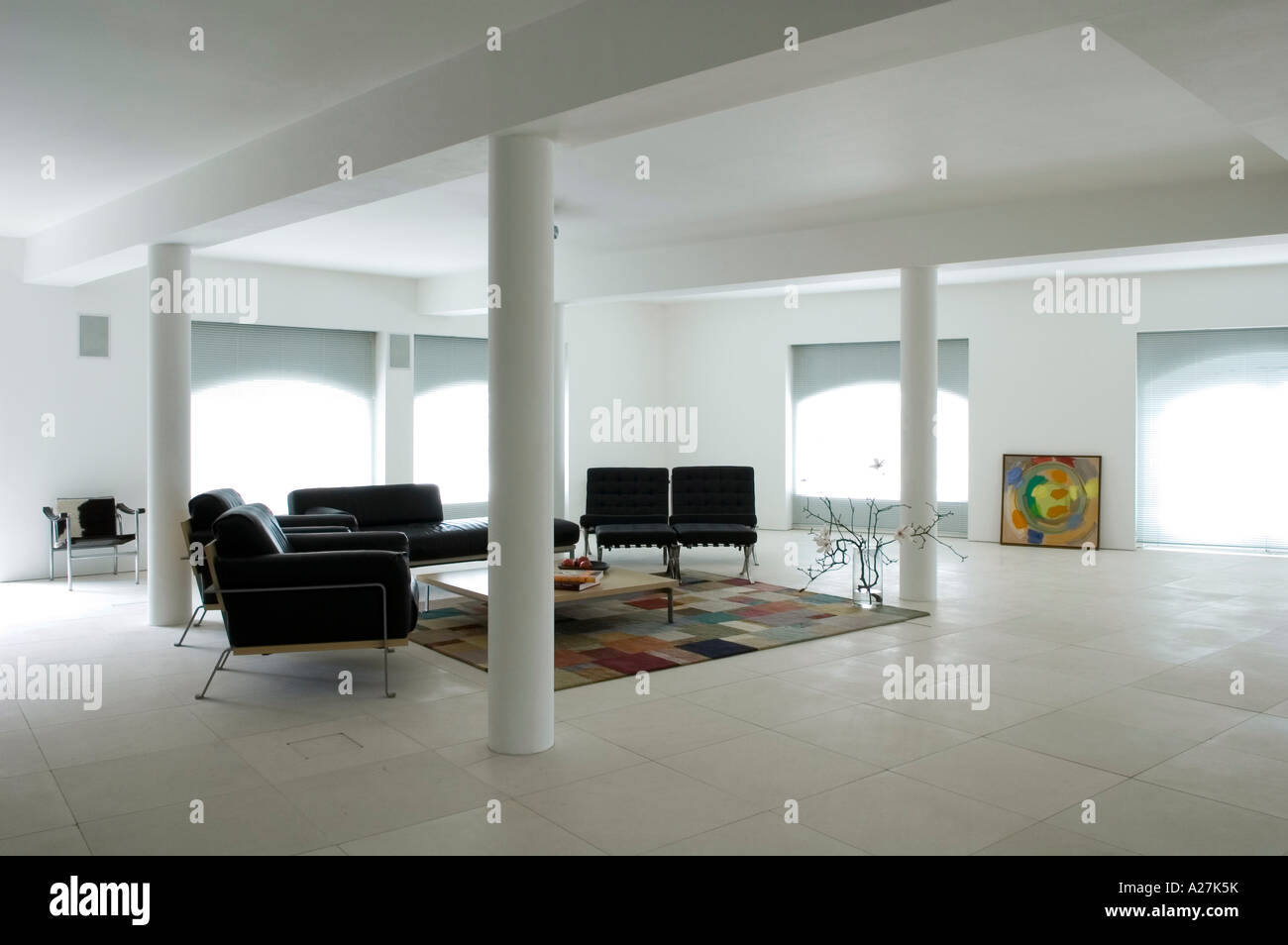 Living area with black seating and interior columns in minimalist warehouse conversion - Stock Image