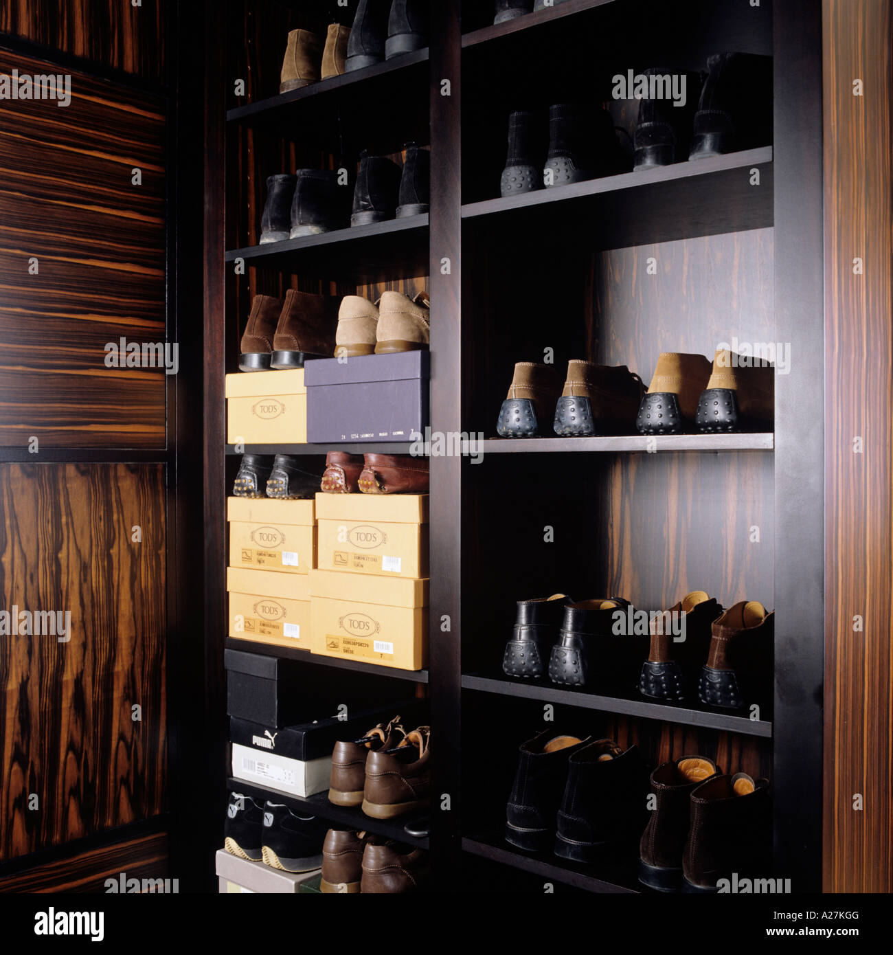 Pairs of shoes stacked neatly on shelves in a walnut cupboard - Stock Image