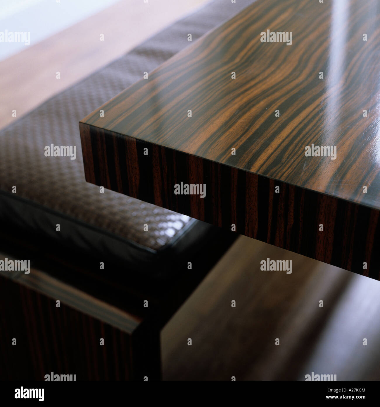 Corner edge of a polished wooden table - Stock Image