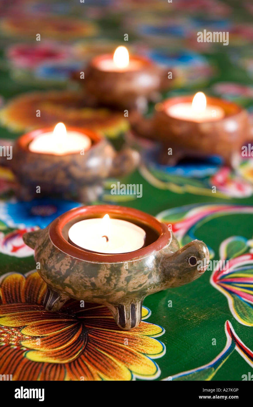 Turtle tealight holders on patterned Mexican tablecloth - Stock Image