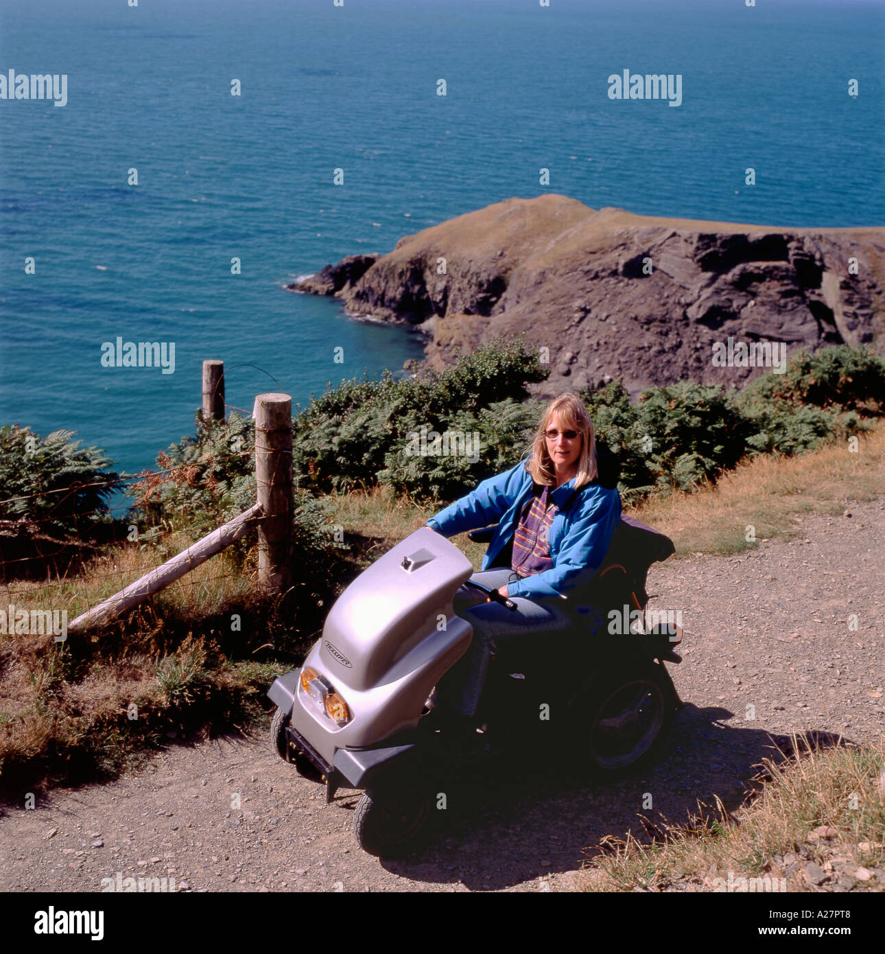 A disabled woman driving an all terrain motorized vehicle on the coastal path Llangranog Ceredigion Wales UK   KATHY DEWITT - Stock Image