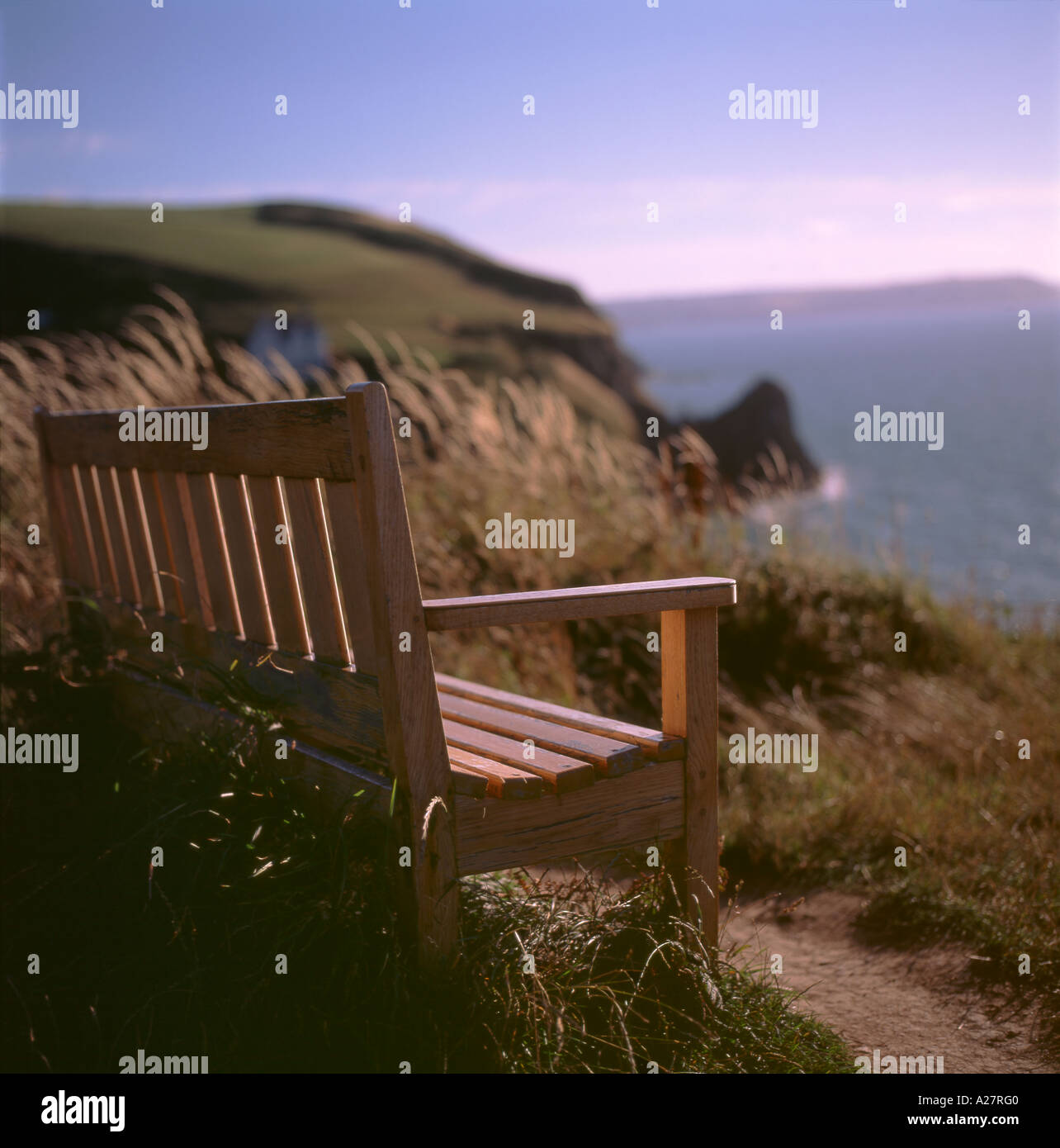 An empty bench overlooking the sea at Llangranog Ceredigion Wales UK - Stock Image
