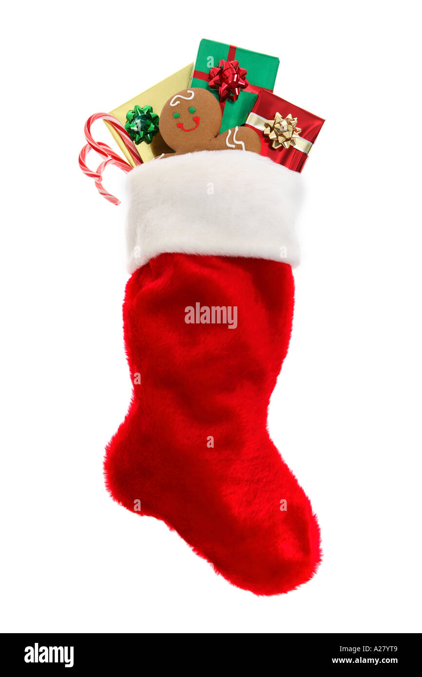 Christmas stocking stuffed with gifts, gingerbread cookie and candy canes. - Stock Image