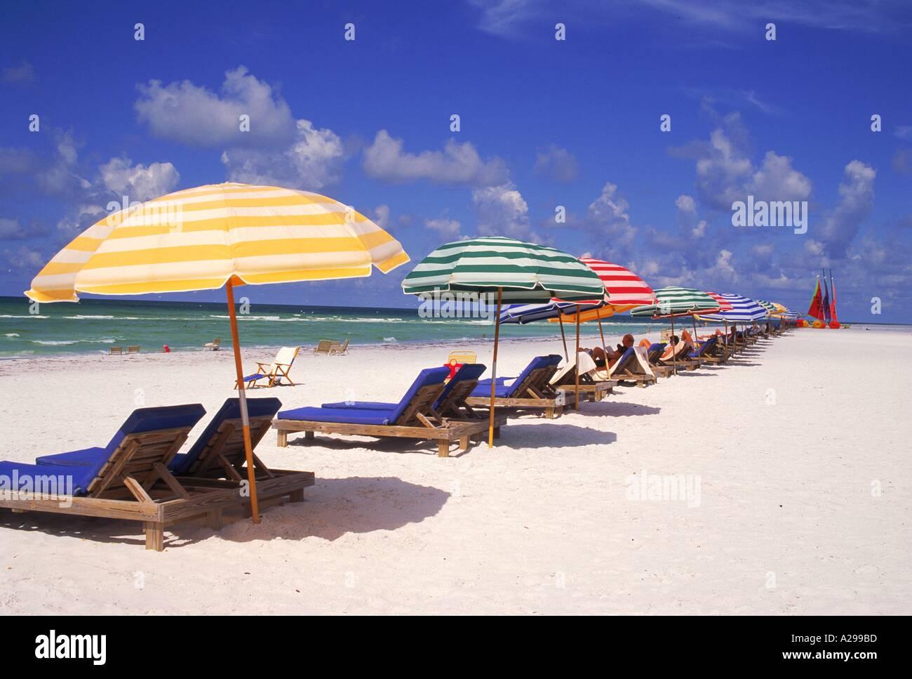 Striped parasols and loungers on beach at Longboat Key Sarasota Florida USA J Miller - Stock Image