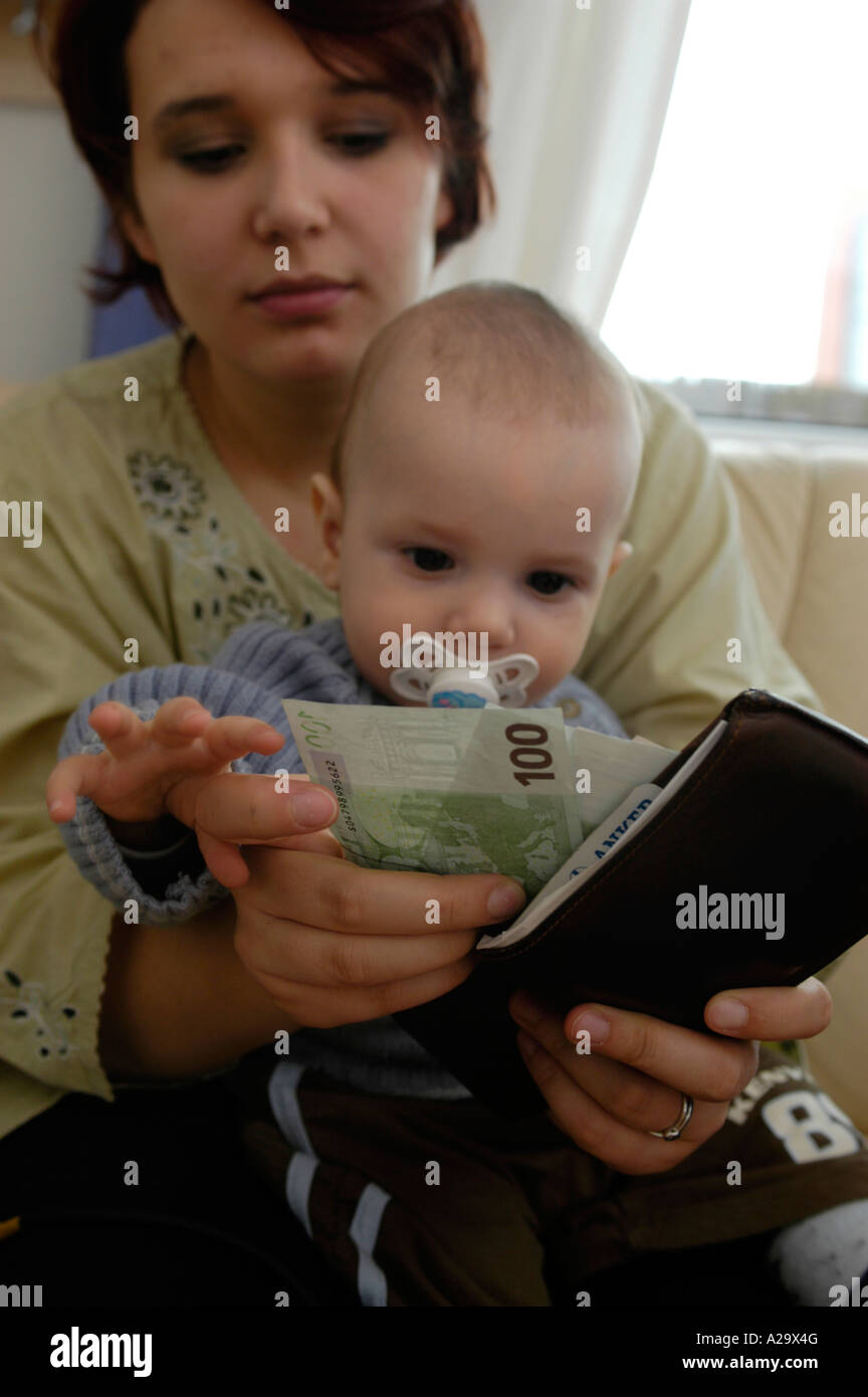 young mother with baby, counting the housekeeping / child allowance, alimonies - Stock Image