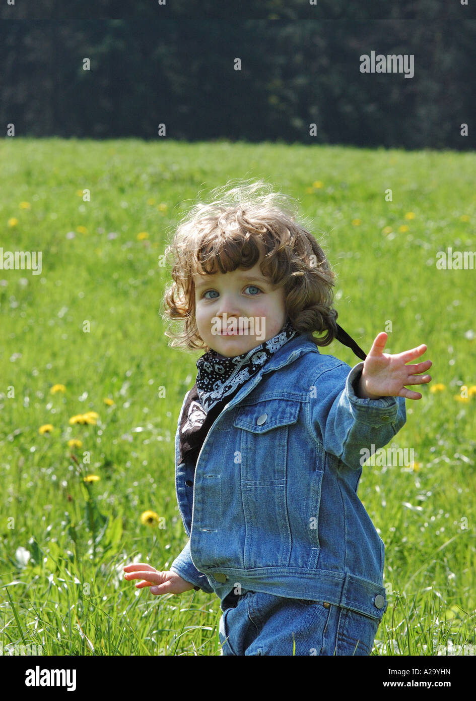 A cute toddler in a hayfield waving to the viewer, as if he/she