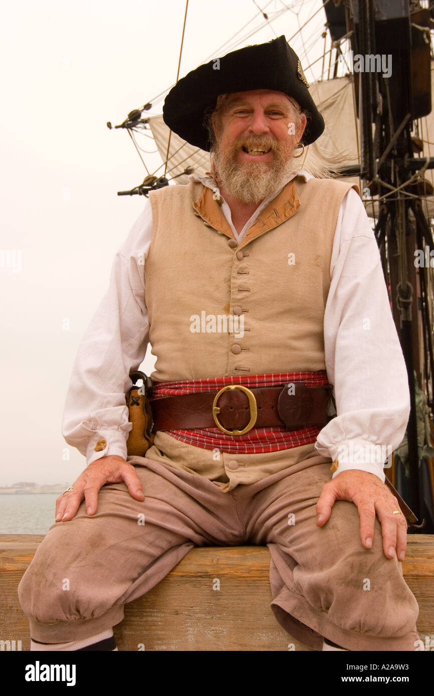 A smiling old pirate sits in front of an authentic tall ship. - Stock Image