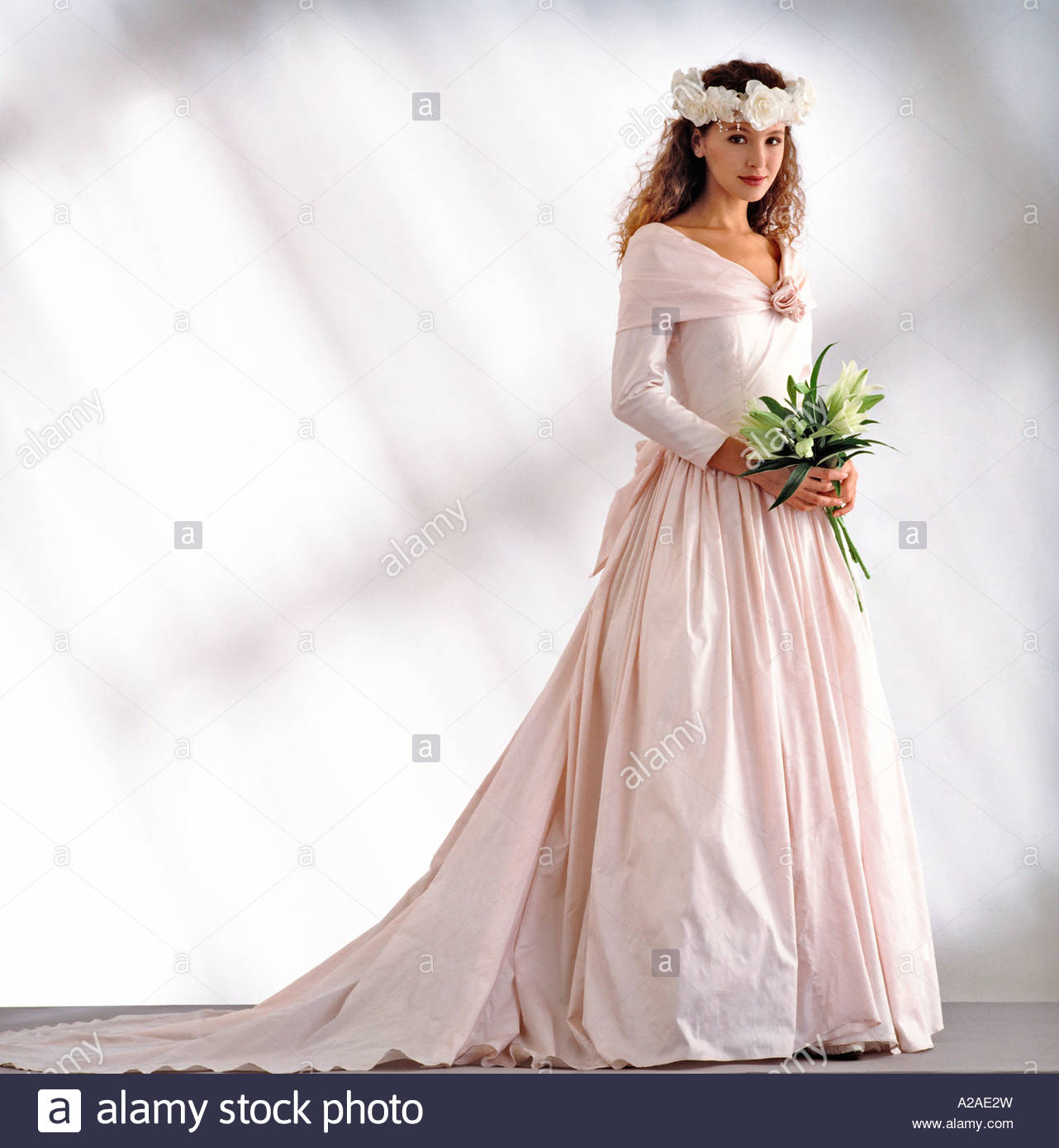 Pretty young bride stands ready in a pale pink wedding dress pretty young bride stands ready in a pale pink wedding dress holding a bouquet of flowers white and grey studio background junglespirit Images